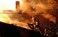A pair of Decatur firefighters work from a ladder as the battle a house fire on Church St. NW.