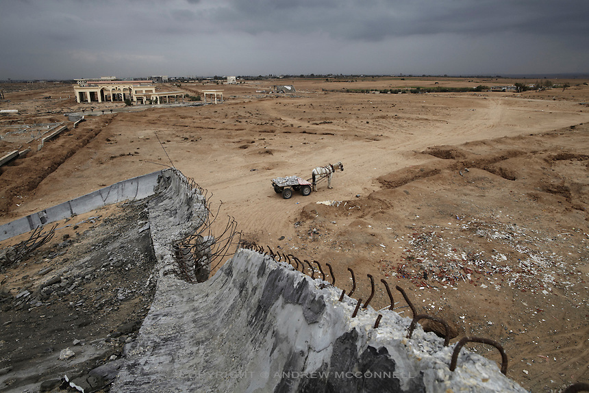 A horse and cart filled with rubble stand in grounds of Yasser Arafat International Airport in southern Gaza. Local men, women, and children work to gather aggregates from underneath the runway and the ruined terminals, for use in concrete, which under the blockade is severely lacking in Gaza.