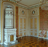 A large tiled stove stands at one end of the Red Salon which is decorated with a frieze of dancing girls based on an engraving by Giocondo Albertolli (c. 1785)
