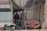 an Iraqi Federal Policeman and Iraqi Army soldier man a combined checkpoint inside the Sadiyah neighborhod in Southwest Baghdad, Iraq August 23, 2010. The number of Iraqi police and army checkpoints across the city has  dramatically increased as Iraqi forces try to gain the upper hand on security now that American combat forces have withdrawn.  .
