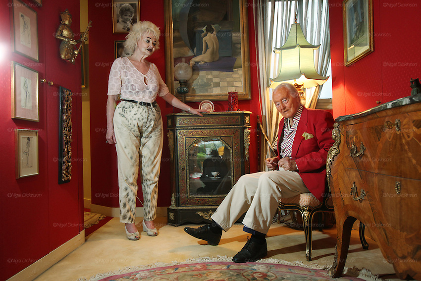 Wolf C Hartwig aged 91, producer of epic films and soft-porn features, with his fourth wife, and actress, Veronique Vendell in their apartment on Avenue de Foch, Paris. Wolf Hartwig was awarded a Bambi Award from German Cinema for his film 'The Iron Cross' which was directed by Sam Peckinpah starring James Coburn with Veronique Vendell. A producer working in exploitation genres, soft porn, sex, lurid, violent and sensational features. Other films he produced include 'Horrors from Spider Island'. 'Lady Hamilton' and 'Virgin of the Seven Seas'.//Veronique Vendell with Wolf Hartwig and painting of nude in vestibule
