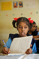 Vijita in class at the Government Girls High School, Venugopalapuram in Cuddalore.. .Vijita (age 14) and Vijyashree (age 11) Viswanathan lost their mother and brother to the tsunami in 2004. They continue to live in the fishing village of Thazanguda with their father Viswanathan, his second wife Kayalvizhi and their two children Sanjay (age 3) and Monica (age 1). ..Until the beginning of the 2009 academic year in June, Vijita and Vijyashree attended the local Thazanguda school. This village school teaches pupils only until the 8th Standard and with Vijita now entering the 9th, it was decided that the two daughters remain together and both travel 3km to the local town school: the Government Girls High School, Venugopalapuram in Cuddalore. ..At the same time Viswanathan decided he would cease day-to-day care of his daughters and place them in the Government Home for Tsunami Children, also in Cuddalore. This was not a move welcomed by either Vijita or Vijyashree and one afternoon after just two weeks at the orphanage, the two girls ran away. At roll call in the orphanage that evening the alarm was sounded and the two sisters were eventually located in Thazanguda waiting for their father and Kayalvizhi who were both away at the time. Realising his daughters' unhappiness, Viswanathan then took them out of the Government home. ..According to her class teacher, Vijita often compares her step-mother to her mother and concludes that she wants her mother back. Vijita confides in her teachers that her stepmother is forever demanding that she and her sister Vijyashree undertake housework. This frustration at home is tempered by the genuine love both sisters have for their father and two younger siblings Sanjay and Monica. Vijita expresses a lonelyness without her mother. Pushpavalli concludes that &quot;Vijita wants something else beyond the love of her father and sister&quot;. ..Viswanathan appears genuinely to want the best for his two elder daughters. His experiment enrolling them at 
