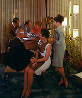 Well dressed couples gathered around the piano in the Admiral Motel lobby.