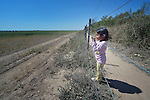 Soli Marita, a 3-year old Wichi indigenous girl, looks through the fence that separates a giant soy bean plantation from Lote 75, an indigenous neighborhood of Embarcacion, Argentina. The Wichi in this area, largely traditional hunters and gatherers, have struggled for decades to recover land that has been systematically stolen from them by cattleraisers and large agricultural plantations.