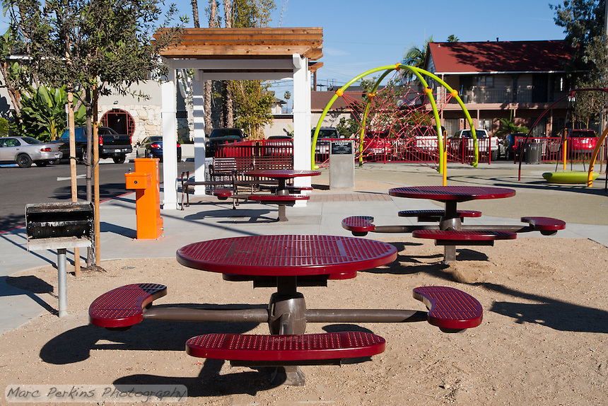 The picnic area at Circle Park, a small pocket park in Anaheim, CA.  Visible are tables, a barbecue, water fountain, pergola, and play structures.