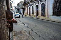 A young Cuban boy lies on the balustrade watching the street of Santiago de Cuba, Cuba, 28 July 2008. About 50 years after the national rebellion, led by Fidel Castro, and adopting the communist ideology shortly after the victory, the Caribbean island of Cuba is the only country in Americas having the communist political system. Although the Cuban state-controlled economy has never been developed enough to allow Cubans living in social conditions similar to the US or to Europe, mostly middle-age and older Cubans still support the Castro Brothers' regime and the idea of the Cuban Revolution. Since the 1990s Cuba struggles with chronic economic crisis and mainly young Cubans call for the economic changes.