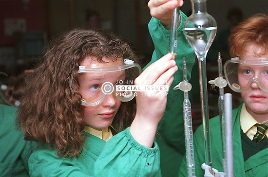 Secondary school girls wearing protective safety goggles and overalls carrying out chemistry experiment in science class,