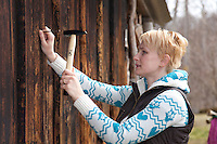 Close-up of young caucasian woman hammering nail into old wooden wall