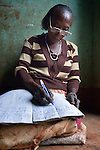 A woman checks her personal accounting in Lukaya, Uganda, where she participates in a women's savings group. The Good Samaritan Women's Project has helped women here to improve their financial literacy, thus improving the quality of life for the women, many of whom are widows who also care for children who lost their parents to AIDS. The program was funded by the Call to Prayer and Self-Denial of United Methodist Women.