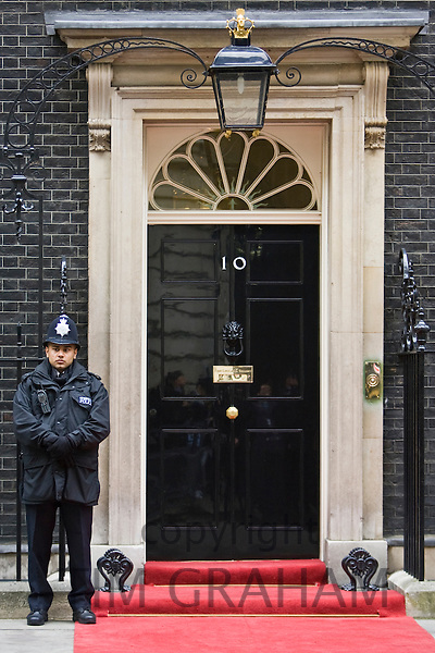 Armed policeman guards Number 10 Downing Street, official home of the British Prime Minister, London, UK