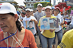 Maria de Jesus Silva Velasquez (right) holds two photos of disappeared family members during a December 16, 2013 demonstration in the southern Mexico city of Tapachula. A Nicaraguan, Silva was part of a caravan of 45 people from Central America who spent 17 days touring 14 Mexican states in search of their loved ones, most of whom had disappeared while following the migrant trail north. <br /> <br /> Silva holds photos of her daughter Jacqueline Silva Giron, who was kidnapped by traffickers in 2004 at the age of 11. Silva has identified the woman responsible for the abduction, but has been unable to locate her daughter for nine years. The second photo she holds is of her nephew Humberto Mayorga Silva, who left in 2007 when he went to search for Silva's daughter. He last called in 2011 but hasn't been heard from since.