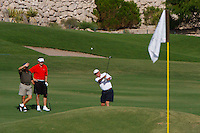 A golfer chips his shot up on to the green.