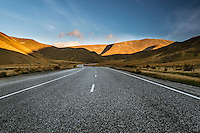 Wide angle view of the Lindis Pass highway as it snakes towards rolling mountains at sunset in Central Otago, New Zealand
