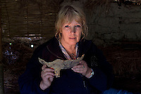 SAVEOCK WATER, CORNWALL, ENGLAND - AUGUST 03: A portrait of archaeologist Jacqui Wood on August 3, 2008 in Saveock Water, Cornwall, England. Inside her replica Bronze Age Roundhouse she is holding a fragment of an iron cauldron found in a votive pool which she dates between the medieval period to the 17th century (no carbon dating)(Photo by Manuel Cohen)