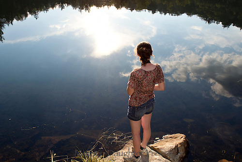 Revelation: Young woman looks out across a pond and the crystal reflection of the trees and sky, New Hampshire, USA