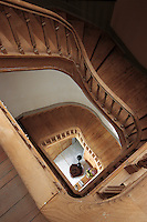 A view down the curved beechwood staircase to the entrance hall far below