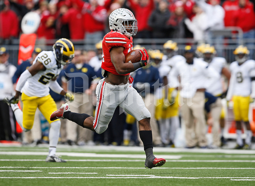 Ohio State Buckeyes running back Ezekiel Elliott (15) runs ahead of Michigan Wolverines defensive back Jourdan Lewis (26) for a 44-yard touchdown during the 4th quarter of the NCAA football game at Ohio Stadium on Nov. 29, 2014. (Adam Cairns / The Columbus Dispatch)