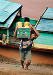 A man unloading produce from a boat at Luang Prabang, Laos on the Mekong river.
