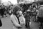 Young teenage girl cradling in her arm her pet Poodle dog as she walks down the street. Roman Road market, East London England 1975
