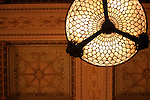 Looking up at a painted ceiling and a lamp in the Chicago Cultural Center.