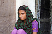 Sadma Khan, 19, sits at the entrance to her shared single-room house in the shared compound of her mother's extended family's house in a slum area of Tonk, Rajasthan, India, on 19th June 2012. She was married at 17 years old to Waseem Khan, also underaged at the time of their wedding. The couple have an 18 month old baby and Sadma is now 3 months pregnant with her 2nd child and plans to use contraceptives after this pregnancy. She lives with her mother since Waseem works in another district and she can't take care of her children on her own. Photo by Suzanne Lee for Save The Children UK