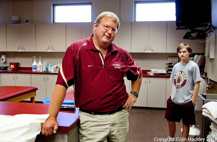 TALLAHASSEE, FLA.7/14/11-LUNT071411 CH-Sam Lunt, associate director of Sports Medicine for Florida State University, is joined by his son Ryan, age 13, in the training room July 14, 2011 in Tallahassee. Lunt is now the dean of trainers at Florida State, he has been the head trainer for the Men's basketball team for 22 years with four more years prior to that as a general trainer for FSU..COLIN HACKLEY PHOTO