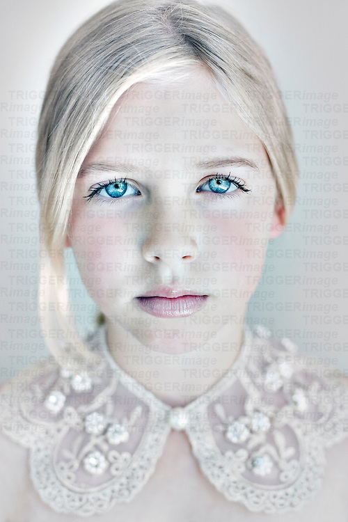 Headshot of young girl with  clear blue eyes and blonde hair wearing white lace looking at camera