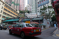 Red taxi cabs on street near Man Mo temple in Hong Kong