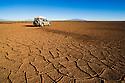 Bolivia, Altiplano, 4x4 vehicle crossing dry lagoon with mud cracks