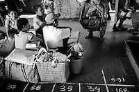 A vendor tries to sell her goods to passengers waiting for a large ship to carry them from the Yangon, back to their homes on the small islands that outlie it.