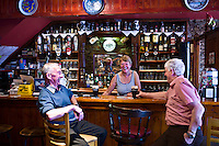 Grainne laughing with locals at her traditional Irish bar, Grainne's, in Mill Street, Timoleague, West Cork, Ireland