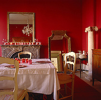 This dining room has been painted a dramatic red