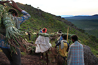 The team is read. Carrying smokers on their shoulders, men climb the last few meters to reach the holy cliff. Life of the Irulas is very religious, and every activity starts with ceremonies to worship ancestor, forest deities and Hindu gods.