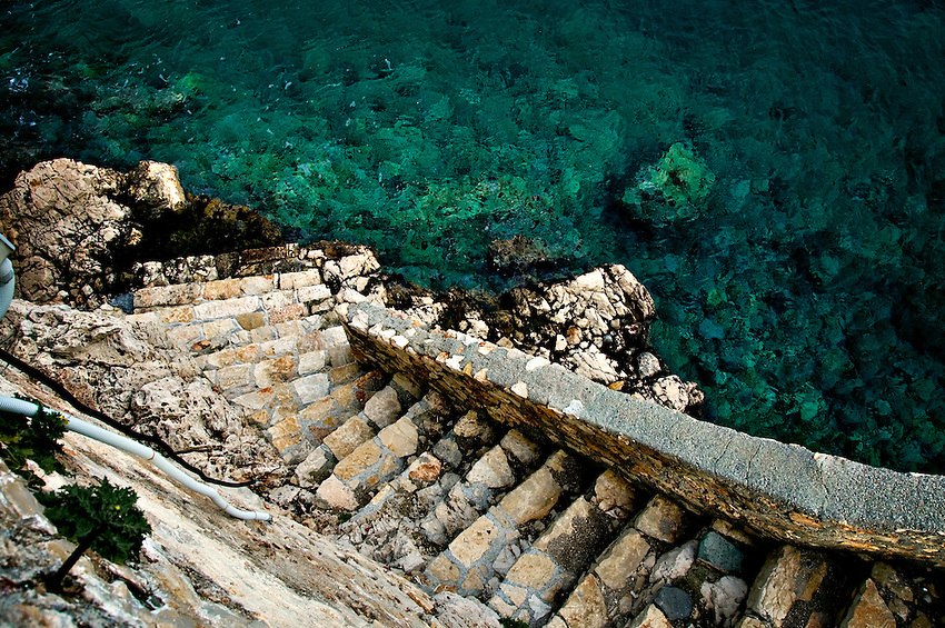 In Meis, Greece, ancient looking rock stairs lead down into the Mediterranean sea of beautiful blue green water.