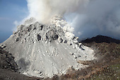 Degassing Rerombola lava dome of Paluweh Volcano during 2012 eruption with ash cloud following rockfall event, Flores, Indonesia.