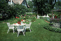 Summer Garden with white wrought iron furniture table and chairs, lawn grass and house, wishing well in yard, flowers, picket fence for beautiful backyard living