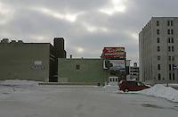 Flint, la cittadina nei pressi di Detroit resa famosa dal film di Michael Moore sulla crisi della General Motors. Paesaggio urbano. Uno spiazzo innevato in mezzo a degli edifici. Cartelloni pubblicitari e un auto parcheggiata.