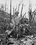 Members of a Marine demolitions crew, assigned to blasting forward enemy positions on Peleliu, evacuate one of their comrades wounded by a Japanese sniper. Note the bullet hole in the steel helmet he is clutching.