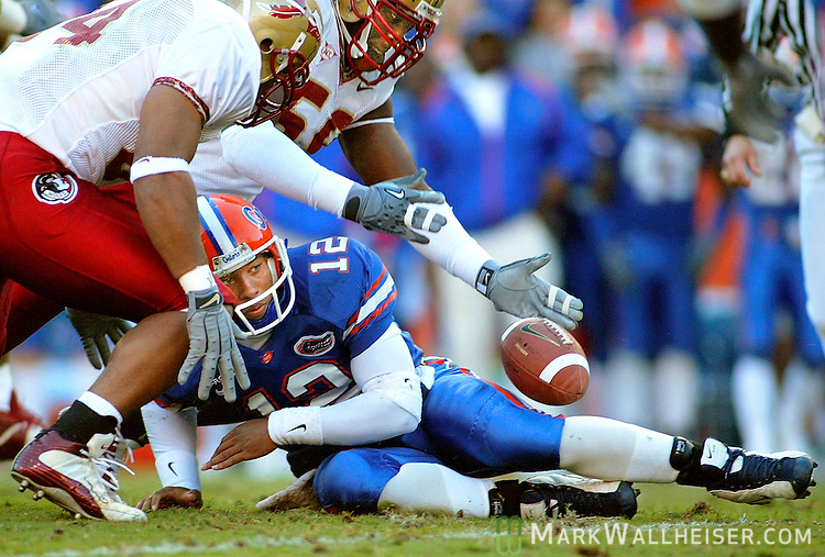University of Florida quarterback Chris Leak (12) watches as FSU's Chauncey Davis (L) and Charles Howard (R) go after his fumble in Tallahassee, Florida November 29, 2003.