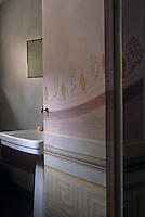Delicate frescos cover the walls and the door leading to this simple ensuite bathroom