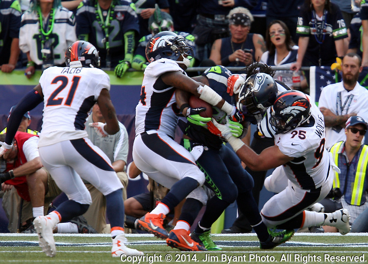 Denver Broncos defensive end Derek Wolfe (95), and linebacker Brandon Marshall (54) move in to tackle Seattle Seahawks running back Marshawn Lynch in the end zone for a safety in the fourth quarter at CenturyLink Field in Seattle, Washington on September 21, 2014. The Seahawks won 26-20 in overtime.    ©2014. Jim Bryant Photo. All rights Reserved.