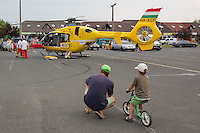Father and son watch as rescue helicopter lands in a car park to help save a life in danger at Balatonlelle (about 140 km South-West of capital city Budapest), Hungary on July 18, 2015. ATTILA VOLGYI