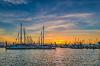 We took this photo of the sunrise over the marina in Corpus Christi Texas.  The sunrise was just peaking up and gave a nice pink/orange glow over the water of the bay and just a hint of light over the sailboats and other boats dock in the marina.