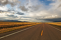long stretch of road in the montana country side, highway 287, dark clouds and blue skies, fields of wheat