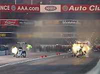 Nov 12, 2016; Pomona, CA, USA; NHRA top fuel driver J.R. Todd (right) explodes an engine on fire alongside Antron Brown during qualifying for the Auto Club Finals at Auto Club Raceway at Pomona. Mandatory Credit: Mark J. Rebilas-USA TODAY Sports