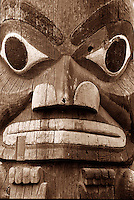 Dramatic close-up of face in totem carving on door of Longhouse, Thunderbird Park, downtown Victoria, BC.