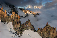 Aiquille Verte and other craggy peaks in the foreground with Mont Blanc rising above morning fog and clouds in the background..