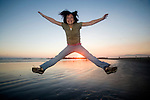 Happy young woman jumps for joy on a beach in California at dusk.