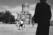 Young Uzbek boys play football in front of the Bibi-Khanym mausoleum, in Samarkand, the old Silk Road trading route city, Uzbekistan