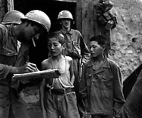 Two North Korean boys, serving in the North Korean Army, taken prisoner in the Sindang-dong area by elements of the 389th Inf. Regt., are interrogated by a U.S. soldier shortly after their capture.  September 18, 1950. Pfc. Francis Mullin. (Army)<br /> NARA FILE #:  111-SC-348805<br /> WAR &amp; CONFLICT BOOK #:  1494